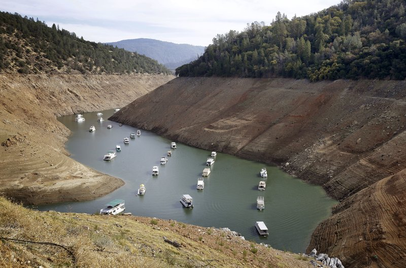 FILE - In this Thursday, Oct. 30, 2014, file photo, houseboats float in the drought-lowered waters of Oroville Lake near Oroville, Calif. Voters will decide whether California borrows nearly $9 billion for water infrastructure projects in the state where its scarcity often pits city dwellers, farmers, anglers and environmentalists against one another. Proposition 3 on the ballot Tuesday, Nov. 6, 2018 would direct the money to storage and dam repairs, watershed and fisheries improvements, and habitat protection and restoration. (AP Photo/Rich Pedroncelli, File)