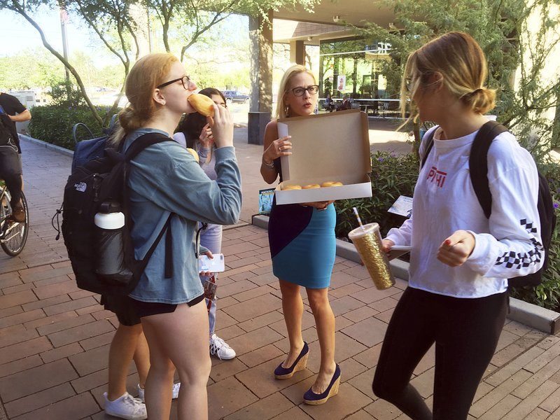 CORRECTS TO DOWNTOWN PHOENIX CAMPUS NOT TEMPE -  Democratic Senate candidate Kyrsten Sinema hands out doughnuts to Arizona State University students on the campus in downtown Phoenix, Monday, Nov. 5, 2018. Sinema, a congresswoman who teaches at the school, closed out her campaign against Republican Rep. Martha McSally with a dash across the Phoenix metro area. (AP Photo/Nicolas Riccardi)