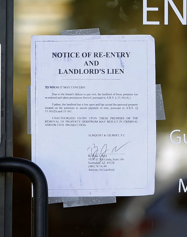 A notice sign is seen at a polling station, Tuesday, Nov. 6, 2018 in Chandler, Ariz. A new polling station opened four hours late after the original location did not open due to the buildings' foreclosure overnight. (AP Photo/Rick Scuteri)