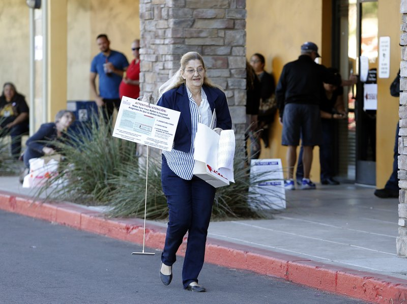 A volunteer moves supplies to a relocated polling station, Tuesday, Nov. 6, 2018 in Chandler, Ariz. The new polling station opened four hours late after the original location did not open due to the buildings' foreclosure overnight. (AP Photo/Rick Scuteri)