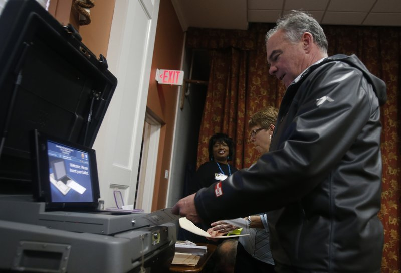 Sen. Tim Kaine, D-Va., feeds his ballot into the vote counting machine as he votes in Richmond, Va., Tuesday, Nov. 6, 2018. Kaine is running against Republican Corey Stewart. (AP Photo/Steve Helber)