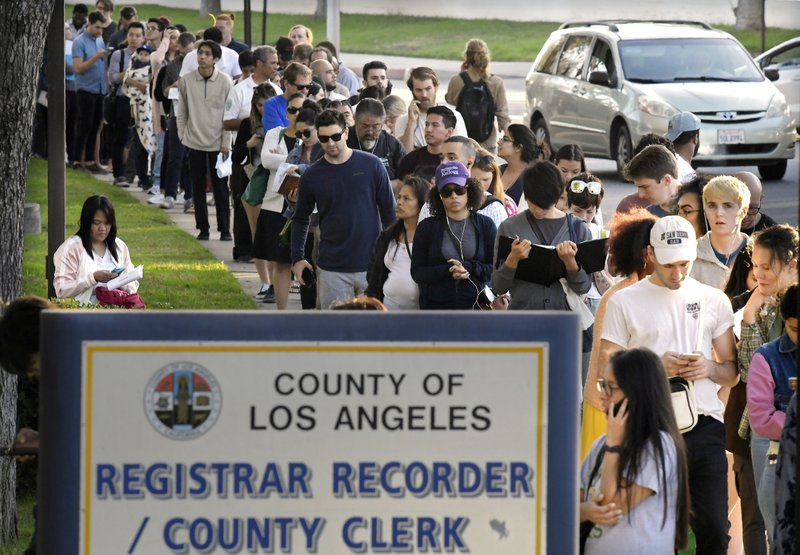 Potential voters wait in long lines to register and vote at the Los Angeles County Registrar's office Tuesday, Nov. 6, 2018, in the Los Angeles section of Los Angeles. A spokesman with the registrar's office says the line at its headquarters in Norwalk is wrapping around the building and that wait times were at about two hours Tuesday. (AP Photo/Mark J. Terrill)
