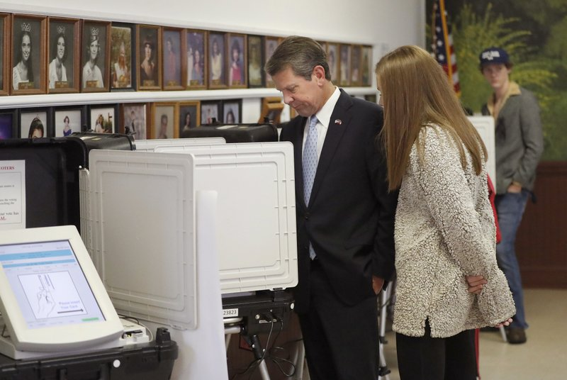 Georgia Republican gubernatorial candidate Brian Kemp casts his ballot as his youngest daughter Amy Porter looks on Tuesday, Nov. 6, 2018, in Winterville, Ga. Kemp is in a close race with Democrat Stacey Abrams. (AP Photo/John Bazemore)