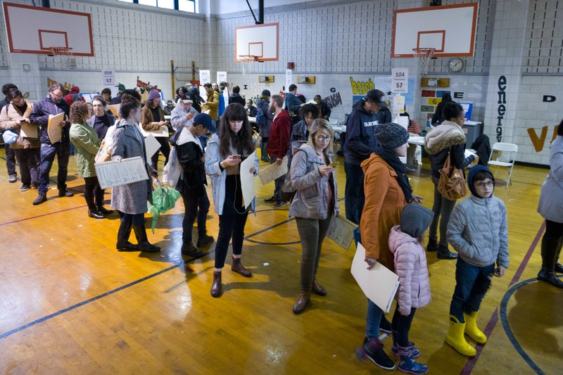 Voters stand in line to cast their ballots at P.S. 22, Tuesday, Nov. 6, 2018, in the Prospect Heights neighborhood in the Brooklyn borough of New York. Earlier in the day four vote scanning machines reportedly broke down at this location. (AP Photo/Mark Lennihan)