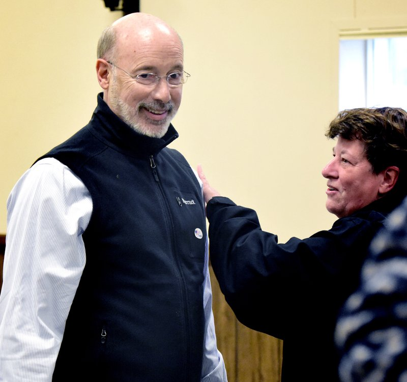Gov. Tom Wolf, left, is greeted by a voter at the Eagle Fire Company poll in Mount Wolf, Pa., on midterm Election Day, Tuesday, Nov. 6, 2018. Wolf voted there with his wife Frances. (Bill Kalina photo/York Dispatch via AP)