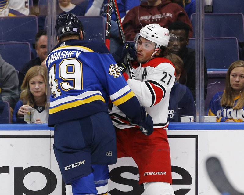 Carolina Hurricanes' Justin Faulk, right, is checked into the boards by St. Louis Blues' Ivan Barbashev, of Russia, during the second period of an NHL hockey game Tuesday, Nov. 6, 2018, in St. Louis. (AP Photo/Billy Hurst)