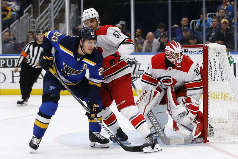 St. Louis Blues' Alexander Steen, left, battles with Carolina Hurricanes' Trevor van Riemsdyk for position in front of goaltender Curtis McElhinney during the second period of an NHL hockey game Tuesday, Nov. 6, 2018, in St. Louis. (AP Photo/Billy Hurst)