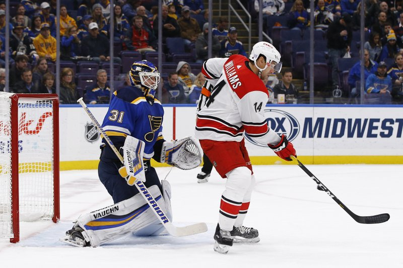 Carolina Hurricanes' Justin Williams, right, deflects a shot in front of St. Louis Blues goaltender Chad Johnson during the first period of an NHL hockey game Tuesday, Nov. 6, 2018, in St. Louis. (AP Photo/Billy Hurst)
