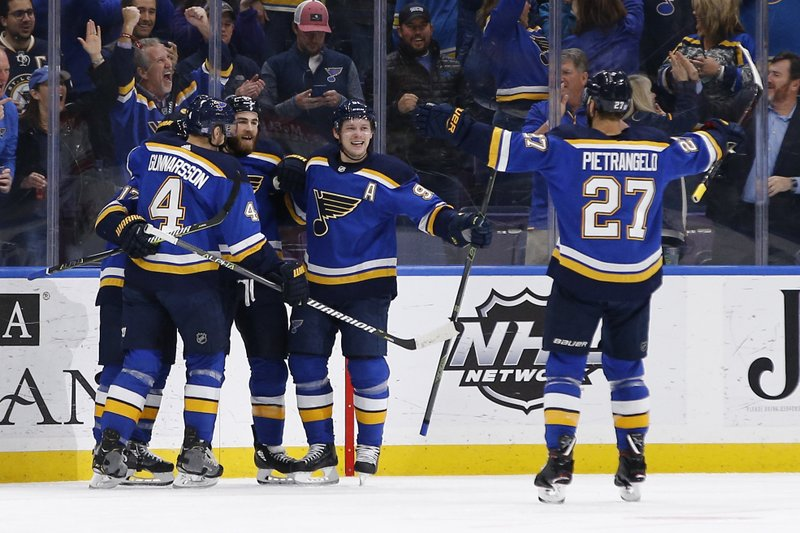 St. Louis Blues' Ryan O'Reilly (90) celebrates with teammates Carl Gunnarsson, of Sweden, (4), Vladimir Tarasenko, of Russia, (91) and Alex Pietrangelo (27) after scoring a goal against the Carolina Hurricanes during the first period of an NHL hockey game Tuesday, Nov. 6, 2018, in St. Louis. (AP Photo/Billy Hurst)