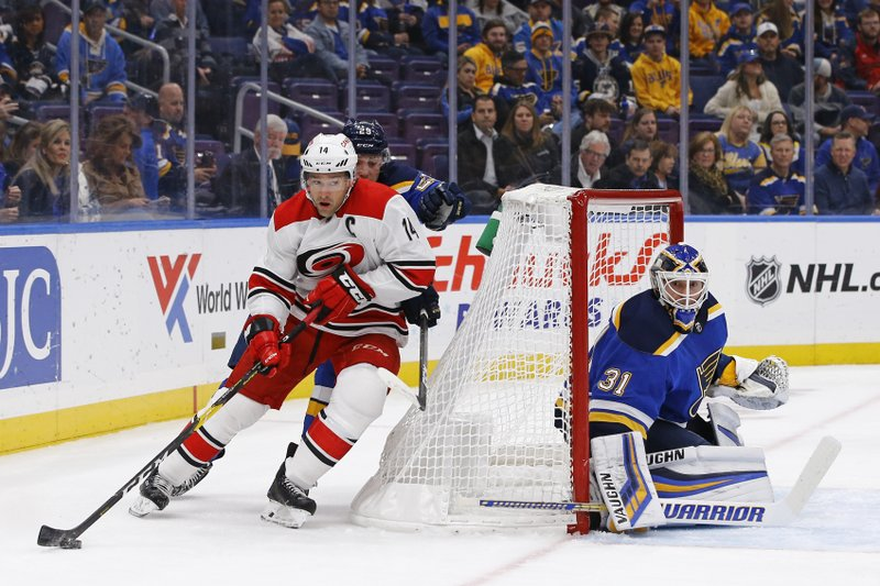 Carolina Hurricanes' Justin Williams, left, looks to get off a shot as he is pressured by St. Louis Blues' Vince Dunn, as goaltender Chad Johnson defends the net during the first period of an NHL hockey game Tuesday, Nov. 6, 2018, in St. Louis. (AP Photo/Billy Hurst)