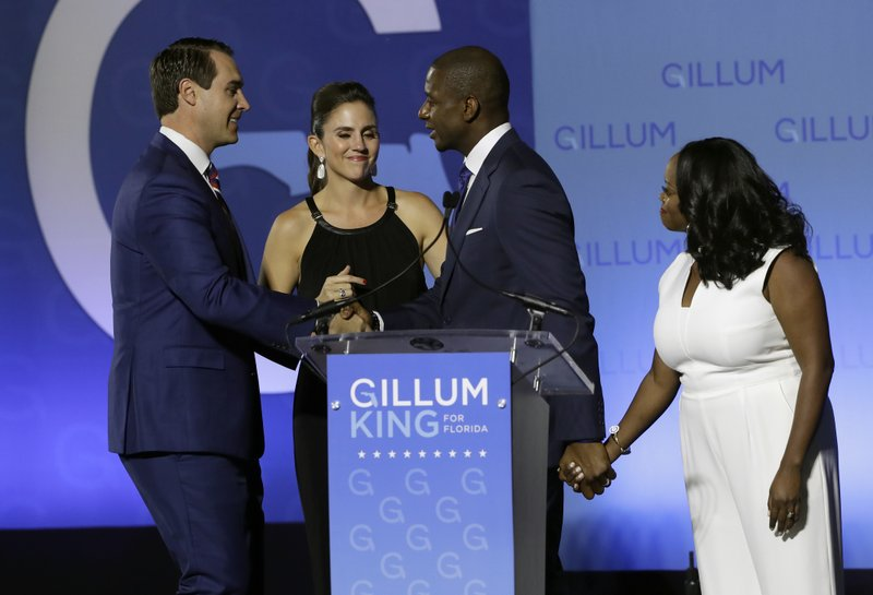 Florida Democratic gubernatorial candidate Andrew Gillum, second from right, shakes hands with running mate Chris King, left, as their wives Kristen King, second from left and R. Jai Gillum, right, look on after Gillum delivered his concession speech Tuesday, Nov. 6, 2018, in Tallahassee, Fla. Gillum lost to Republican former U.S. Rep. Ron DeSantis. (AP Photo/Chris O'Meara)