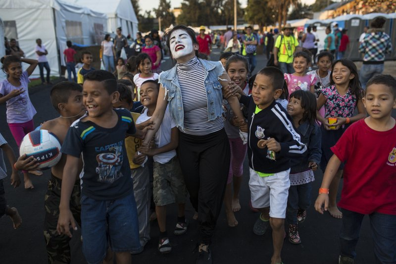 A woman performs as a mime for Central American migrant children at the Jesus Martinez stadium in Mexico City, Tuesday, Nov. 6, 2018. Humanitarian aid converged around the stadium in Mexico City where thousands of Central American migrants winding their way toward the United States were resting Tuesday after an arduous trek that has taken them through three countries in three weeks. (AP Photo/Rodrigo Abd)