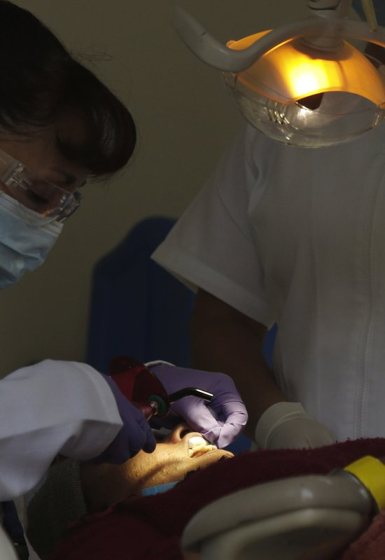 A Central American migrant receives a dental checkup in a shelter at the Jesus Martinez stadium in Mexico City, Tuesday, Nov. 6, 2018. Humanitarian aid converged around the stadium in Mexico City where thousands of Central American migrants winding their way toward the United States were resting Tuesday after an arduous trek that has taken them through three countries in three weeks. (AP Photo/Marco Ugarte)