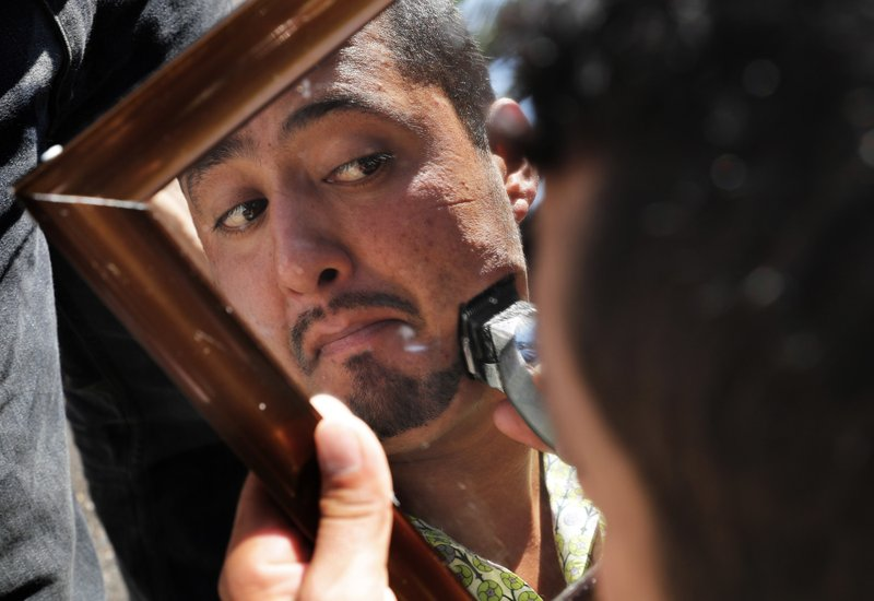 A Central American migrant trims his facial hair in a shelter at the Jesus Martinez stadium in Mexico City, Tuesday, Nov. 6, 2018. Humanitarian aid converged around the stadium in Mexico City where thousands of Central American migrants winding their way toward the United States were resting Tuesday after an arduous trek that has taken them through three countries in three weeks. (AP Photo/Marco Ugarte)