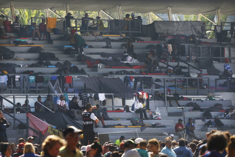 Central American migrants settle in a shelter at the Jesus Martinez stadium in Mexico City, Tuesday, Nov. 6, 2018. Humanitarian aid converged around the stadium in Mexico City where thousands of Central American migrants winding their way toward the United States were resting Tuesday after an arduous trek that has taken them through three countries in three weeks. (AP Photo/Marco Ugarte)