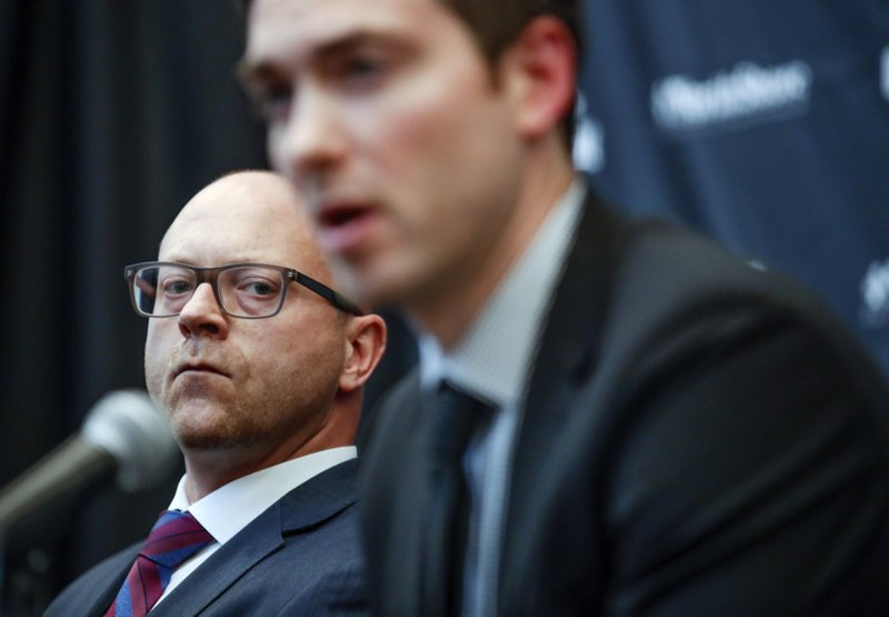Chicago Blackhawks Senior Vice President and General Manager Stan Bowman, left, listens as new head coach Jeremy Colliton speaks during an NHL hockey press conference Tuesday, Nov. 6, 2018, in Chicago. Colliton replaces Joel Quenneville who was fired on Tuesday. (AP Photo/Kamil Krzaczynski)