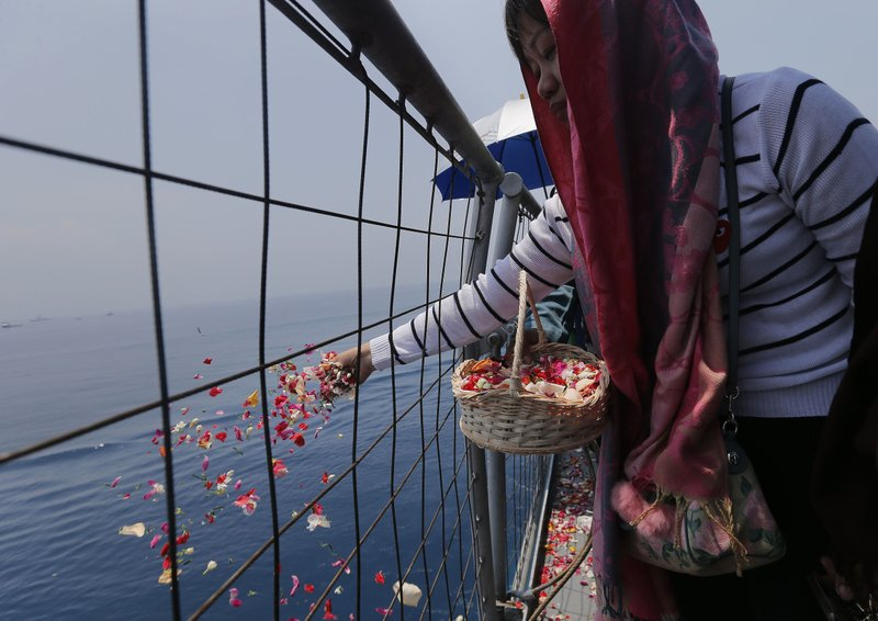 A relative sprinkles flowers for victims in the crashed Lion Air flight 610 aboard an Indonesia Navy ship in the waters where the airplane is believed to have crashed in Tanjung Karawang, Indonesia, Tuesday, Nov. 6, 2018. (AP Photo/Tatan Syuflana)