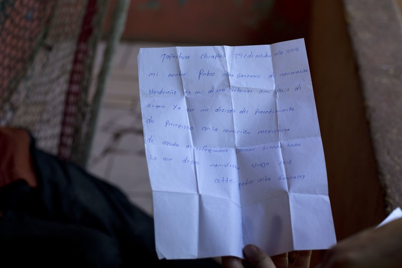 """In this Nov. 1, 2018 photo, Pablo Alba shows a letter he wrote and signed voluntarily accepting his deportation, during an interview in his home in San Pedro Sula, Honduras. Alba choked up thinking about how his 11-year-old son wrapped his arms around his neck and begged to be taken on the journey north. Alba said no, not wanting the boy to risk the arduous trek. """"If there must be suffering, I will go alone,"""" he said, recalling that Oct. 13 day when he set off to join the caravan with only the clothes on his back. (AP Photo/Moises Castillo)"""