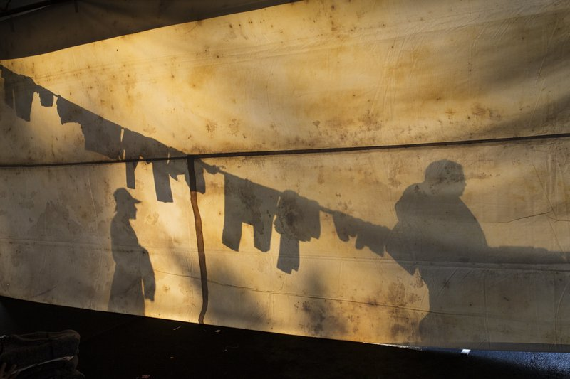 The silhouettes of Central American migrants are projected on the side of a tent at the Jesus Martinez stadium in Mexico City, Tuesday, Nov. 6, 2018. Humanitarian aid converged around the stadium in Mexico City where thousands of Central American migrants winding their way toward the United States were resting Tuesday after an arduous trek that has taken them through three countries in three weeks. (AP Photo/Rodrigo Abd)