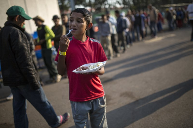 Dennis Mauricio Suarez, 12, from Honduras, eats breakfast at the Jesus Martinez stadium in Mexico City, Wednesday, Nov. 7, 2018. Central American migrants on Wednesday continued to straggle in for a rest stop at a Mexico City stadium, where about 4,500 continue to weigh offers to stay in Mexico against the desire of many to reach the U.S. border. (AP Photo/Rodrigo Abd)