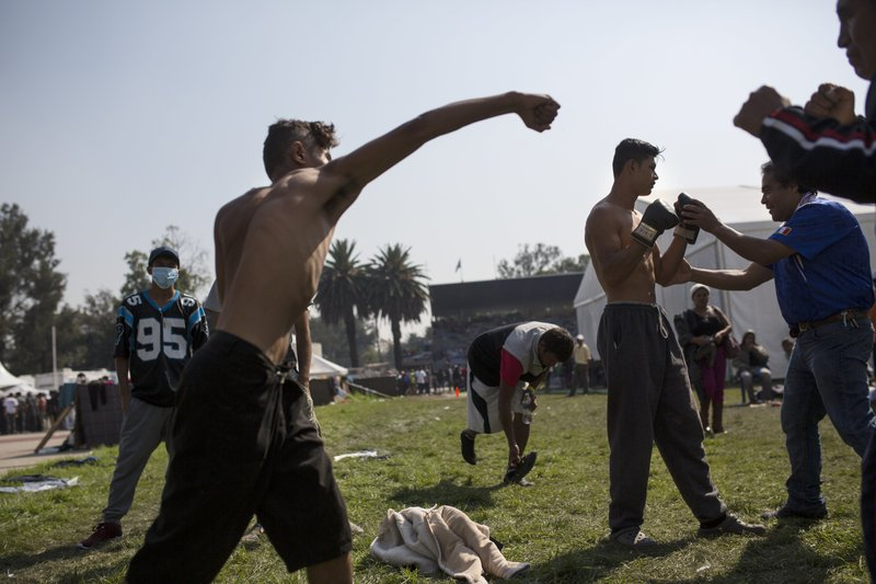 A Central American migrant shadowboxes during a rest day at the Jesus Martinez stadium in Mexico City, Wednesday, Nov. 7, 2018. Central American migrants on Wednesday continued to straggle in for a rest stop at a Mexico City stadium, where about 4,500 continue to weigh offers to stay in Mexico against the desire of many to reach the U.S. border. (AP Photo/Rodrigo Abd)