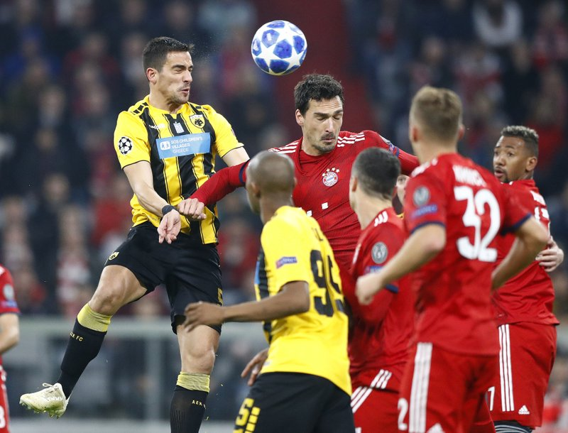 Bayern defender Mats Hummels, center, and AEK's Vasileios Lampropoulos jump for the ball during the Champions League group E soccer match between FC Bayern Munich and AEK Athen in Munich, Germany, Wednesday, Nov. 7, 2018. (AP Photo/Matthias Schrader)