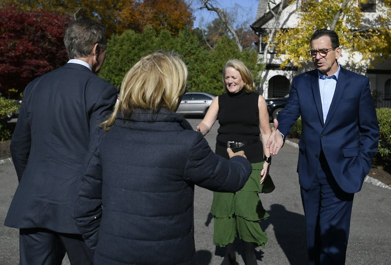 Governor Dannel P. Malloy, right, and wife Cathy, greet Connecticut's new governor-elect Ned Lamont, left, and wife Annie Lamont at the Governor's residence for lunch in Hartford, Conn., Thursday, Nov. 8, 2018. (AP Photo/Jessica Hill)