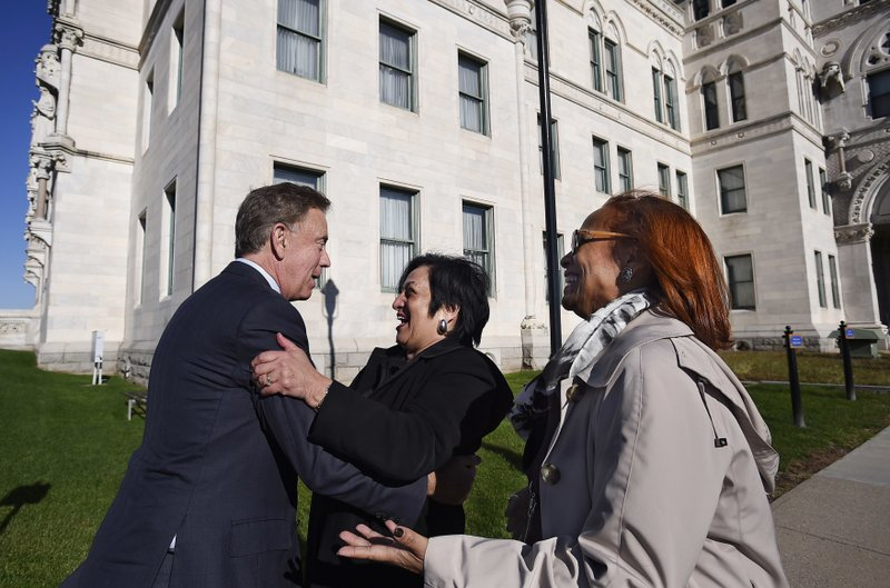 Connecticut's new governor-elect Ned Lamont embraces Dr. Elsa Nunez as State Rep. Toni Walker, D-New Haven, right, looks on before a news conference to introduce them as part of his transition team at the State Capitol in Hartford, Conn., Thursday, Nov. 8, 2018. (AP Photo/Jessica Hill)