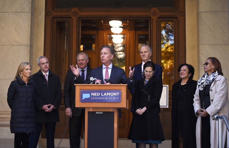 Connecticut's new governor-elect Ned Lamont introduces his transition team during a news conference at the State Capitol in Hartford, Conn., Thursday, Nov. 8, 2018. From the left is wife Annie Lamont and transition team members, Ryan Drajewicz, Connecticut Attorney General George Jepsen, Garrett Moran, Dr. Elsa Nunez, and State Rep. Toni Walker. (AP Photo/Jessica Hill)