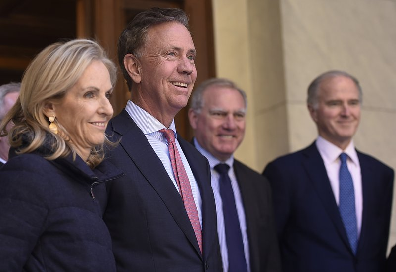 Connecticut's new governor-elect Ned Lamont smiles as he stands with wife Annie, left, during a news conference to introduce his transition team at the State Capitol in Hartford, Conn., Thursday, Nov. 8, 2018. (AP Photo/Jessica Hill)