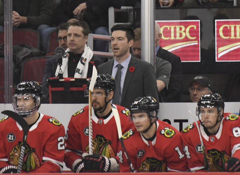 Chicago Blackhawks head coach Jeremy Colliton, center, watches play during the first period of an NHL hockey game against the Carolina Hurricanes Thursday, Nov. 8, 2018, in Chicago. (AP Photo/David Banks)