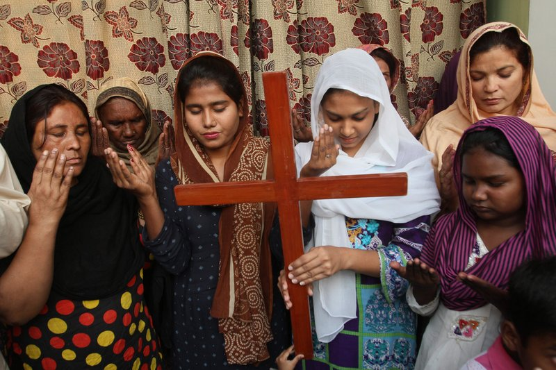 FILE - In this Oct. 31, 2018, file, photo Pakistan Christians pray for Aasia Bibi, a Catholic mother of five who has been on death row since 2010 accused of blasphemy in Multan, Pakistan. The uproar surrounding Aasia Bibi _ a Pakistani Christian woman who was acquitted of blasphemy charges and released from death row but remains in isolation for her protection _ has drawn attention to the plight of the country's Christians.The minority, among Pakistan's poorest, has faced an increasingly intolerant atmosphere in this Muslim-majority nation where radical religious and sectarian groups have become more prominent in recent years. (AP Photo/Irum Asim, File)