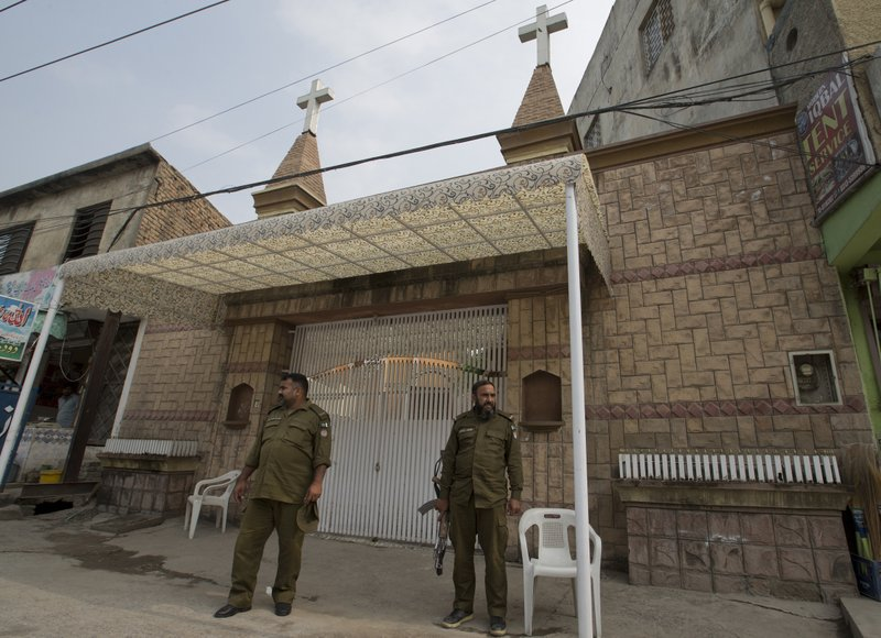 In this Nov2, 2018, photo, Pakistani police officers stand guard outside a church in Rawalpindi, Pakistan. The uproar surrounding Aasia Bibi _ a Pakistani Christian woman who was acquitted of blasphemy charges and released from death row but remains in isolation for her protection _ has drawn attention to the plight of the country's Christians.The minority, among Pakistan's poorest, has faced an increasingly intolerant atmosphere in this Muslim-majority nation where radical religious and sectarian groups have become more prominent in recent years. (AP Photo/B.K. Bangash)