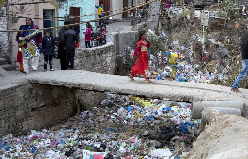 FILE - In this Dec. 25, 2016, file photo, a Pakistani Christian girl crosses a bridge in poor Christian neighborhood in Islamabad, Pakistan.The uproar surrounding Aasia Bibi _ a Pakistani Christian woman who was acquitted of blasphemy charges and released from death row but remains in isolation for her protection _ has drawn attention to the plight of the country's Christians.The minority, among Pakistan's poorest, has faced an increasingly intolerant atmosphere in this Muslim-majority nation where radical religious and sectarian groups have become more prominent in recent years. (AP Photo/B.K. Bangash, File)