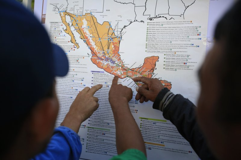 Migrants discuss their journey using a map posted inside the sports complex where thousands of migrants have been camped out for several days in Mexico City, Friday, Nov. 9, 2018. About 500 Central American migrants headed out of Mexico City on Friday to embark on the longest and most dangerous leg of their journey to the U.S. border, while thousands more were waiting one day more at a massive improvised shelter.(AP Photo/Rebecca Blackwell)