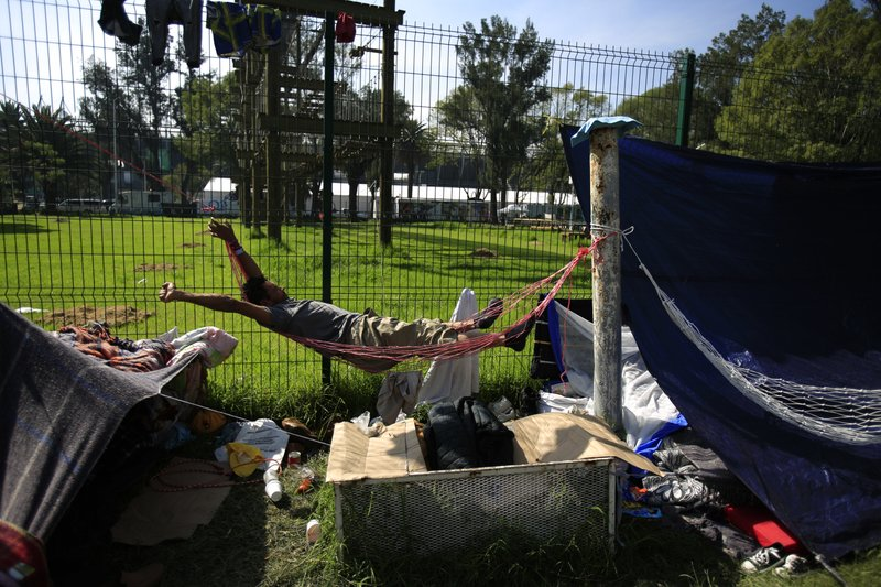 A man stretches as he awakens in a hammock at the sports complex where thousands of migrants have been camped out for several days in Mexico City, Friday, Nov. 9, 2018. About 500 Central American migrants headed out of Mexico City on Friday to embark on the longest and most dangerous leg of their journey to the U.S. border, while thousands more were waiting one day more at a massive improvised shelter. (AP Photo/Rebecca Blackwell)