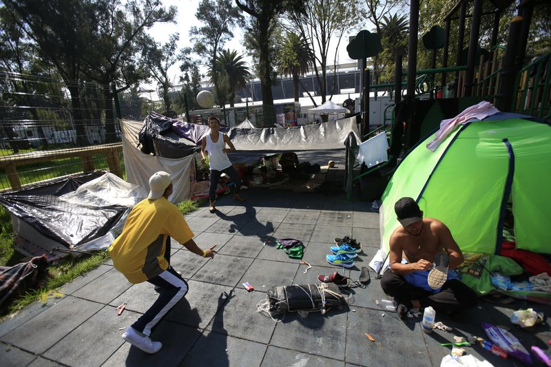 Central American migrants who are part of a group from different countries who banded together on their journey north for safety, and pooled their money to buy two tents, play with a soccer ball as another scrubs his shoes clean with a toothbrush, at the sports complex where thousands of migrants have been camped out for several days in Mexico City, Friday, Nov. 9, 2018. About 500 Central American migrants headed out of Mexico City on Friday to embark on the longest and most dangerous leg of their journey to the U.S. border, while thousands more were waiting one day more at a massive improvised shelter. (AP Photo/Rebecca Blackwell)