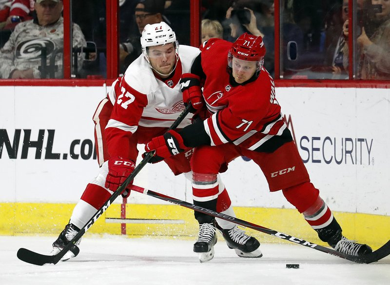 Lucas Wallmark (71) and Michael Rasmussen (27) compete for the puck during the second period of an NHL hockey game Saturday, Nov. 10, 2018, in Raleigh, N.C. (AP Photo/Karl B DeBlaker)
