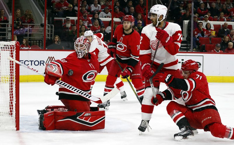 Carolina Hurricanes goaltender Scott Darling (33) watches the puck come off the post with Hurricanes' Lucas Wallmark (71) and Detroit Red Wings' Andreas Athanasiou (72) battling nearby during the second period of an NHL hockey game Saturday, Nov. 10, 2018, in Raleigh, N.C. (AP Photo/Karl B DeBlaker)