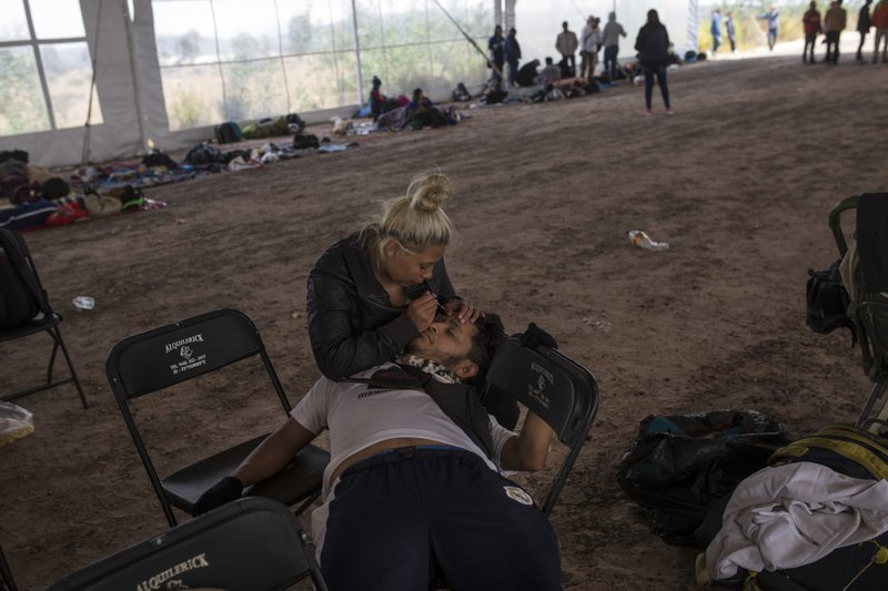 Central American migrant Jenifer Argueta plucks the eyebrows of Honduran Kevin Banegas, while waiting to receive donated food in Palmillas, Mexico, Saturday, Nov. 10, 2018. Thousands of Central American migrants were back on the move toward the U.S. border Saturday, after dedicated Mexico City metro trains whisked them to the outskirts of the capital and drivers began offering rides north. (AP Photo/Rodrigo Abd)