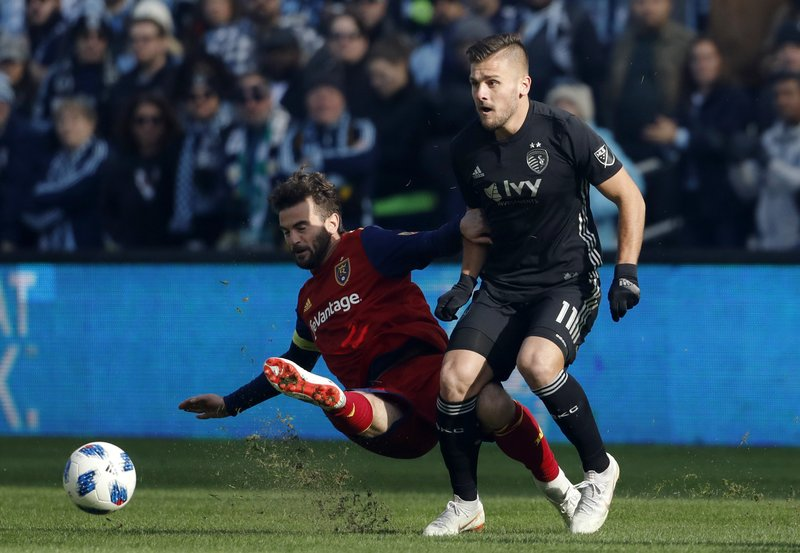 Real Salt Lake midfielder Kyle Beckerman (5) clears the ball away from Sporting Kansas City forward Diego Rubio (11) during the first half of a MLS Western Conference semifinals soccer match in Kansas City, Kan., Sunday, Nov. 11, 2018. (AP Photo/Colin E. Braley)