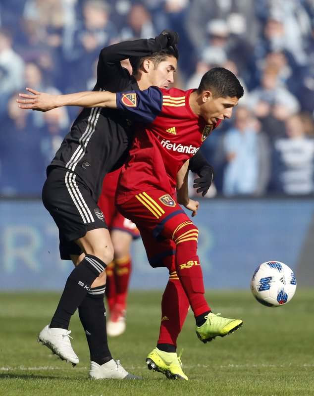 Sporting Kansas City midfielder Felipe Gutierrez, left, and Real Salt Lake forward Jefferson Savarino, right, battle for the ball during the first half of an MLS Western Conference semifinal soccer match in Kansas City, Kan., Sunday, Nov. 11, 2018. (AP Photo/Colin E. Braley)