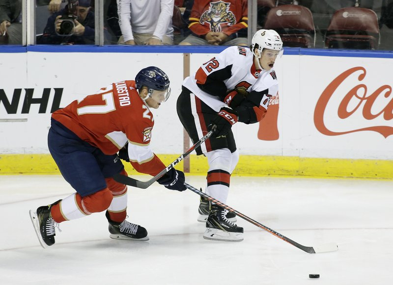 Florida Panthers center Nick Bjugstad (27) and Ottawa Senators defenseman Thomas Chabot (72) fight for the puck during the first period of an NHL hockey game on Sunday, Nov. 11, 2018, in Sunrise, Fla. (AP Photo/Terry Renna)