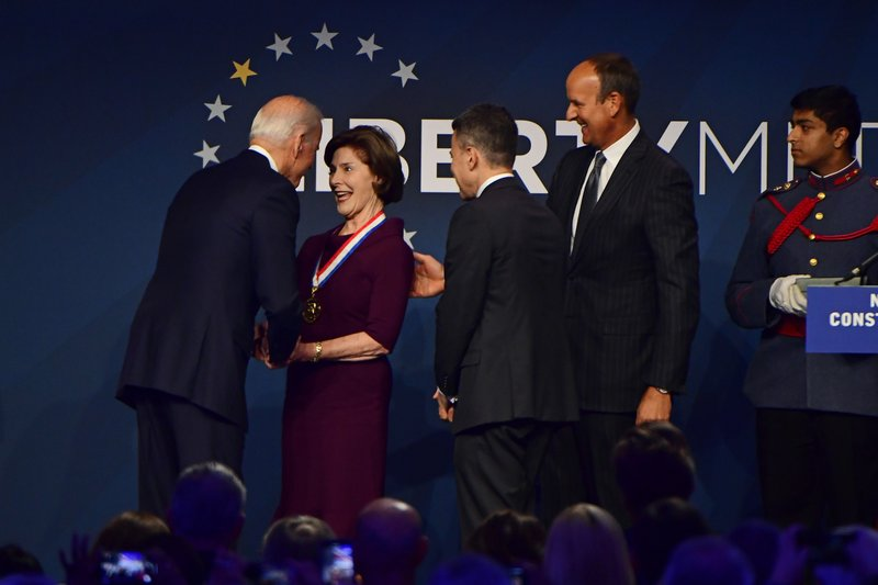 Former U.S. Vice President Joe Biden congratulates former first lady Laura Bush after receiving a medal at the National Constitution Center in Philadelphia, Sunday, Nov. 11, 2018. Former U.S. President George Bush and and Laura Bush received the 30th annual Liberty Medal, an honor given to those who are committed to freedom and human rights globally. (AP Photo/Corey Perrine)