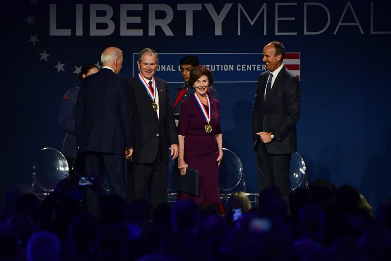 Former U.S. President George Bush, center left, and first lady Laura Bush react after receiving medals from former U.S. Vice President Joe Biden, left, and Doug DeVos, executive committee chairman for the National Constitution Center, at the center in Philadelphia, Sunday, Nov. 11, 2018. The Bush couple received the 30th annual Liberty Medal, an honor given to those who are committed to freedom and human rights globally. (AP Photo/Corey Perrine)