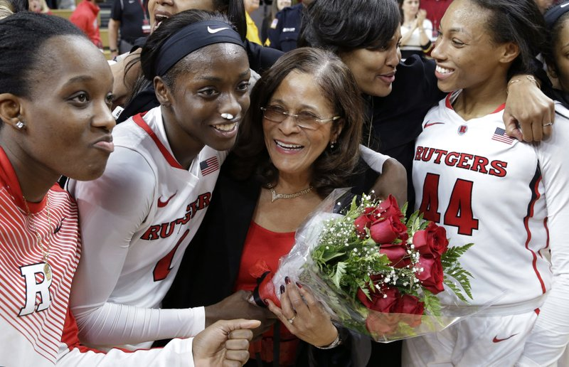 FILE - In this Feb. 5, 2015, file photo, Rutgers coach C. Vivian Stringer, center, holds flowers as she is surrounded by players and assistants after Rutgers won an NCAA college basketball game against Nebraska, 46-43, in Piscataway, N.J. With the win, Stringer became the winningest coach in Big 10 history. Stringer is one victory away from becoming the fifth Division I women's basketball coach to reach 1,000 victories. She'll get her first chance to join the exclusive club Tuesday night, Nov. 13, 2018, against Central Connecticut State. (AP Photo/Mel Evans, File)