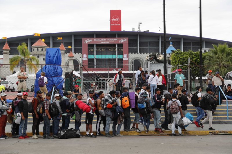 Central American migrants, part of the caravan hoping to reach the U.S. border, line up to enter the Benito Juarez Auditorium , in Guadalajara, Mexico, Monday, Nov. 12, 2018. Several thousand Central American migrants marked a month on the road Monday as they hitched rides toward the western Mexico city of Guadalajara. (AP Photo/Marco Ugarte)