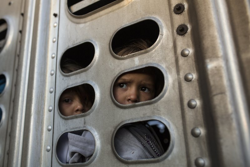 A couple of Central American migrant girls, part of the caravan hoping to reach the U.S. border, get a ride in a chicken truck, in Irapuato, Mexico, Monday, Nov. 12, 2018. Several thousand Central American migrants marked a month on the road Monday as they hitched rides toward the western Mexico city of Guadalajara. (AP Photo/Rodrigo Abd)