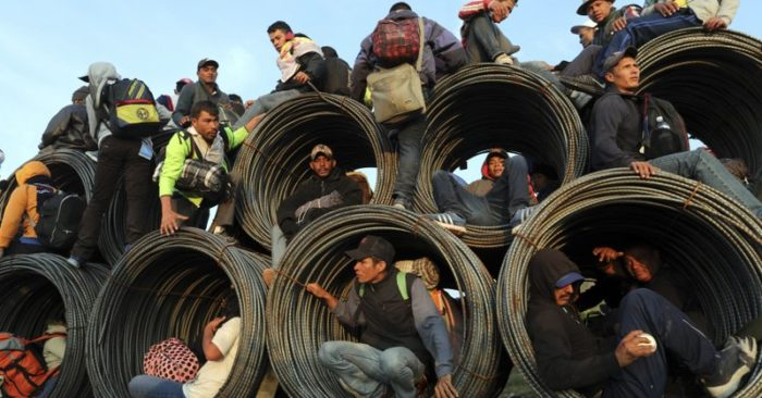Central American migrants, part of the caravan hoping to reach the U.S. border, get a ride on a truck carrying rolls of steel rebar, in Irapuato, Mexico, Monday, Nov. 12, 2018.