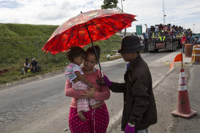 Central American migrant, part of the caravan hoping to reach the U.S. border, wait for the truck to pass by and give them a ride on the road that connects Irapuato with Guadalajara, Mexico, Monday, Nov. 12, 2018. Several thousand Central American migrants marked a month on the road Monday as they hitched rides to the western Mexico city of Guadalajara and toward the U.S. border. (AP Photo/Rodrigo Abd)